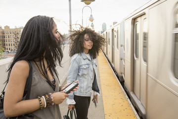 Young women waiting at a train station in Queens, New York
