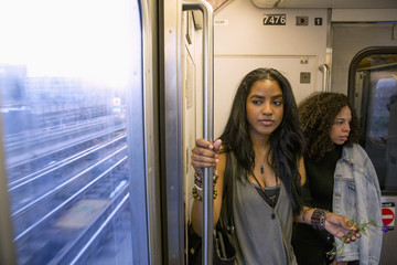 Friends commuting by train in Queens, New York