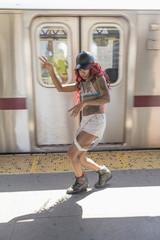 Young woman dancing beside a subway train