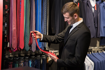 Man is picking up tie for suit in men's shop.