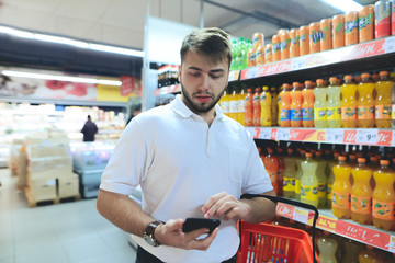 A man with a basket looks at the phone while shopping at a supermarket. Shopping in the store. is in the supermarket near the drinks.