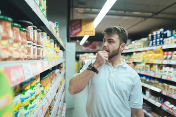 A man thinks what kind of product in a supermarket to choose. The buyer selects canned food at the store. Shopping in a supermarket.