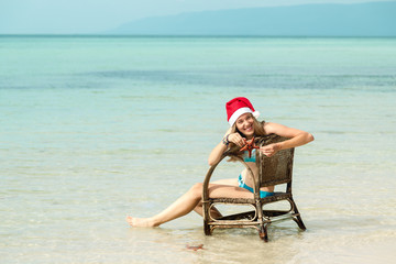 A young woman sits in an armchair by the sea in Santa's Christmas hat, and she holds a starfish