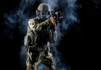 American soldier in combat ammunition with weapon in the hands of equipped laser sights is in battle order.