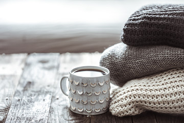 a stack of sweaters and a Cup of tea