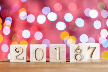 2018 in the foreground, displaces 2017. Christmas card. On bright bokeh background. Copy space for your text.