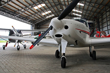 Small private lightweight propeller airplanes in hangar.