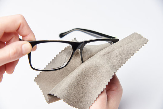 The hands are rubbing the glasses for a view with a napkin