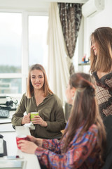 Cheerful young businesswoman is having a coffee break with her colleagues in the office