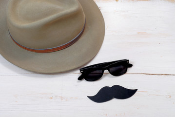Old felt fedora hat on rustic white-washed wooden background with sunglasses and paper cutout mustache for men's health awareness in November.