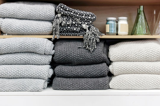 a pile of cotton towels on wooden shelf