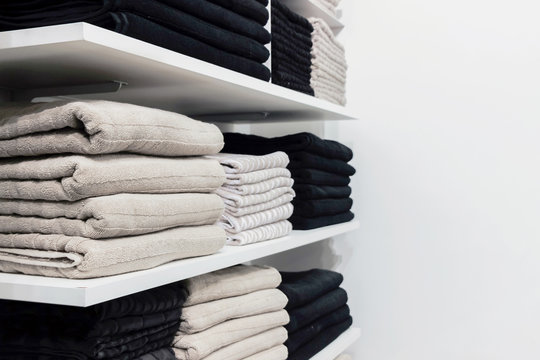 a pile of towels on white shelf