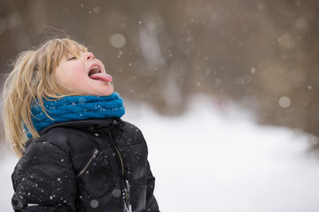 Cute blond kid boy catching snowflakes with his tongue. Walking in a winter park. Child having fun with snow outdoors.