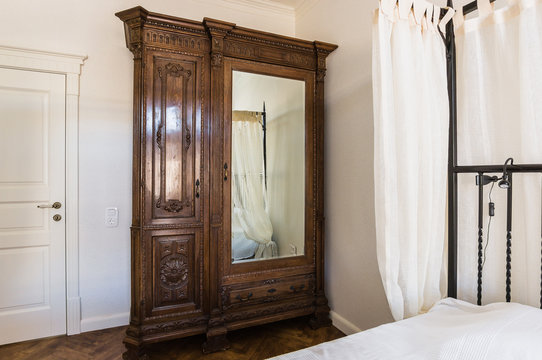 a four-poster bed and an antique wardrobe