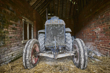 The front of a vintage tractor in an old brick barn with straw floor