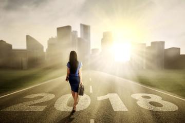 Female entrepreneur walking with numbers 2018