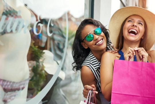 Giggling friends window shopping for underwear