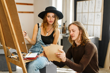 Male artist, in casual torn jeans, consulting his female colleague, in balck hat and denim dangarees, while drawing