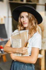 Beautiful long hair artist girl, in a black hat and denim dangarees before the easel