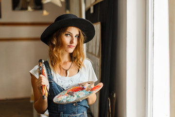 Beautiful long hair artist girl, in a black hat and denim dangarees holding colorful palette before the easel