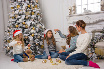 Children and adults in a Santa's hats are decorate a Christmas tree