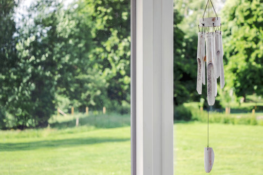 wind chime on window with green garden