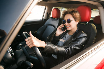 Beautiful business woman in leather jacket is talking on the mobile phone and smiling while driving in a car. Happy busy day in a big city.