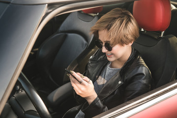Business woman using internet on her mobile phone and s while sitting in the car. News in the internet. Work hard everywhere