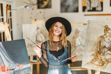 Female artist wears black hat posing near picture indoor the studio Wall mural