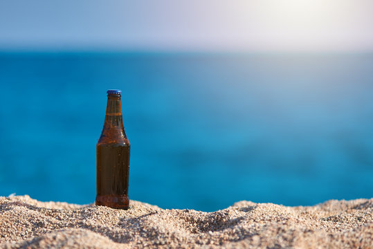 Bottle of beer on the beach sand against the sea.