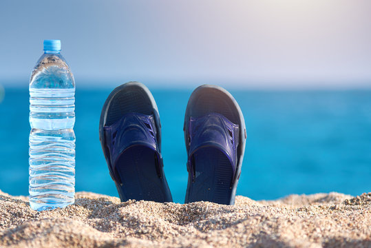 Bottles of pure water and pair of sandals on the beach sand against the sea.