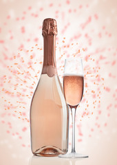 Bottle and glass of pink rose champagne on pink