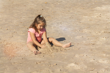 little girl playing in the sand on the seashore