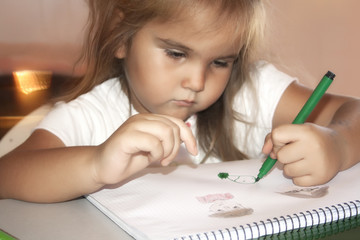 a little girl draws pictures sitting at home