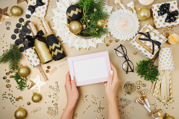 Female hands hold mockup photo frame. Christmas decoration background in golden and black colors. Flat lay, top view