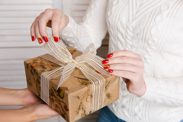 Girl with a Christmas manicure holds a gift in her hands. Red New Year manicure with a gold strip.