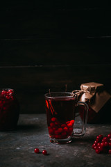 hot tea made from cranberry. Homemade jam in a glass jar on a dark background. Winter christmas drink