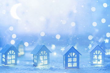 Holiday background with small wooden houses and star garlands.