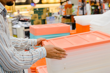 Close up on person going shopping checking or choosing, business shelf service background. Selecting container, factory packaging, goods merchandise purchase, relocation moving process