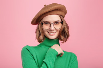 Beautiful french girl looks delightfully into camera, shows white perfect teeth, expresses positiveness, glad to share her success with close people, isolated over pink background. Happiness, beauty Fotomurales