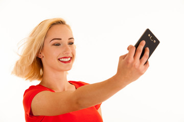 Attractive young blond woman making selfie with her smart phone isolated over white background