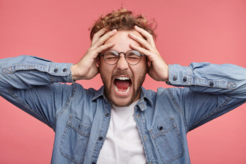 Stressful hipster male scremas in panic, closes eyes in terror, keeps hands on head, finds out terrified news or disaster about best friend, can`t believe of his death. People, stress, annoyance