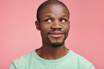 Isolated shot of pleasant looking male with dark skin has moony expression, looks aside up, dreams about something pleasant, isolated over pink background. Happiness and positiveness concept