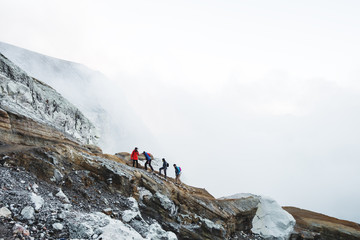 Group of young travelers walking on volcanic mountain, Kawah Ijen crater in Indonesia