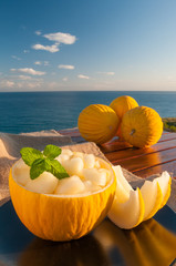Typical mediterranean fruits: yellow melon with blue sea in the background