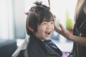 Asian boy getting haircut