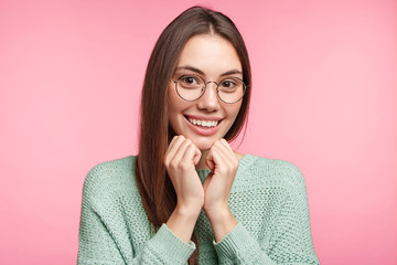 Portrait of delightful glad woman keeps hands under chin, poses against pink background, feels enjoyment and happiness as recieves work about which she dreamt many years, achieves her goal or aim