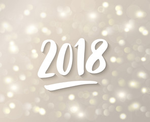 2018 hand drawn numbers. White and gold sparkling glowing lights. Holiday background with bokeh effect.