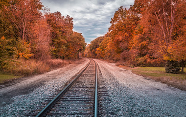 Railway track with a curve and trees in autumn colors, United States