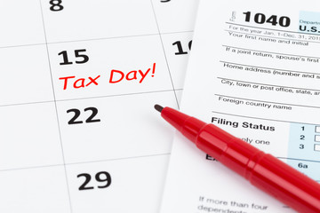 Tax day on calendar with red marker pen, and tax form